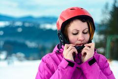 A beautiful woman skier wears a helmet and fixes it for safety stock photo