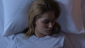Beautiful woman sleeping in bed, relaxing at night after long day, top view. Stock footage stock video