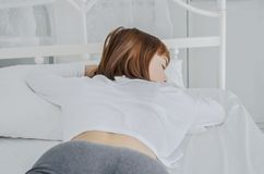 A woman wearing a white dress, she is sleeping. royalty free stock photos