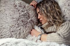 Beautiful woman is sleeping and dreaming on soft bed. At home Stock Photos