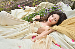 Beautiful woman sleeping with flowers outdoor royalty free stock image