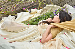 Beautiful woman sleeping with flowers outdoor Stock Photo
