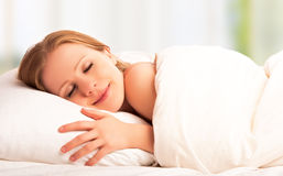 Beautiful woman sleeping and smiles in his sleep in bed. Young beautiful woman sleeping and smiles in his sleep in bed stock images