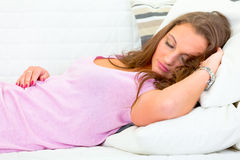 Beautiful woman sleeping on sofa at livingroom Stock Photos