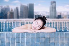 Beautiful woman sleeping in swimming pool. Picture of beautiful woman looks sleep during relaxing in the swimming pool. Shot with modern city background Royalty Free Stock Photos
