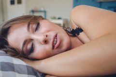 Beautiful girl sleeps in the bedroom, lying on bed royalty free stock photo