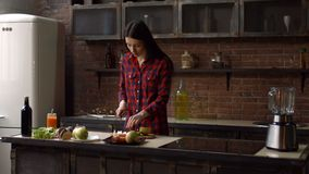 Beautiful woman slicing apple on cutting board. Attractive brunette young housewife slicing apple with knife on wooden cutting board while cooking in domestic stock video