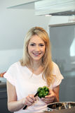 Beautiful woman slicing a green pepper Stock Photos