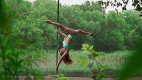 Beautiful Woman with Slim Body Dancing on Background Forest and Lake. Slender Girl Pole Dancer Performs Acrobatic Tricks on Pylon