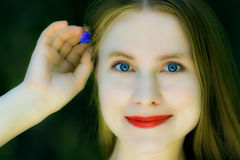 Beautiful woman with a small blue flower Royalty Free Stock Images