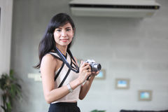 Beautiful woman and small camera on her hand Stock Image