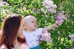 Beautiful woman with small kid. And flowers Royalty Free Stock Images