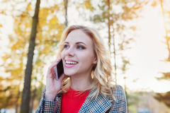 Beautiful woman with smart phone in colorful autumn park. Beautiful young woman in checked coat and red sweater with smart phone in autumn park Royalty Free Stock Photography