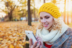 Beautiful woman with smart phone in colorful autumn park. Beautiful young woman in yellow knitted hat, white scarf and checked coat holding smart phone, texting Stock Photos