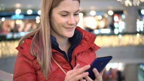 Beautiful woman with smartphone in mall. Browsing internet, communicating with friends. Winter coat. stock video