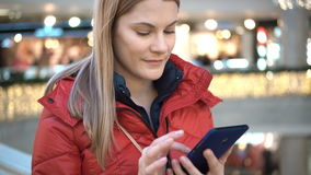 Beautiful woman with smartphone in mall. Browsing internet, communicating with friends. Winter coat. stock footage