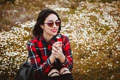 Beautiful woman smelling a daisy. Beautiful woman with sunglasses sitting in the middle of a flowery meadow smelling a daisy stock photography
