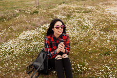 Beautiful woman smelling a daisy. Beautiful woman with sunglasses sitting in the middle of a flowery meadow smelling a daisy stock photos