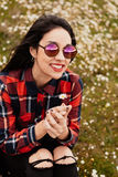 Beautiful woman smelling a daisy. Beautiful woman with sunglasses sitting in the middle of a flowery meadow smelling a daisy royalty free stock photography