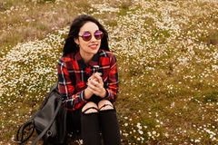 Beautiful woman smelling a daisy. Beautiful woman with sunglasses sitting in the middle of a flowery meadow smelling a daisy royalty free stock photo