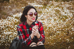 Beautiful woman smelling a daisy. Beautiful woman with sunglasses sitting in the middle of a flowery meadow smelling a daisy stock image