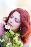 Beautiful woman smells at a christmas rose. Beautiful redheaded woman smells at a christmas rose Stock Photos