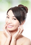 Beautiful woman smile face with clean face skin. And health teeth, and finger touch her face, concept for skin care and dental hygiene; over nature green Royalty Free Stock Photography