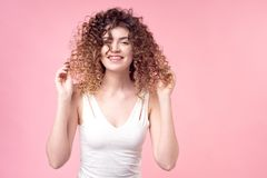 Beautiful woman with a smile on face with amazing curls in a white T-shirt deloet laying of the hand holds accessories stock photography