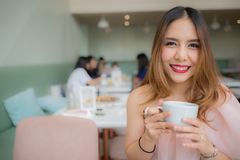 Beautiful woman smile and holding a cup of coffee in her hand at coffee shop stock image