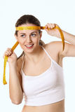 Beautiful woman smiles with funny expression and measuring tape. Weight control concept Stock Images