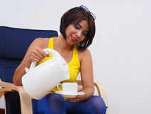 Beautiful woman smiles pouring water Stock Photography