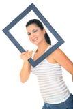 Beautiful Woman Smiling. Beautiful young woman posing through empty frame royalty free stock photos