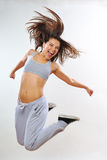 Beautiful woman smiling. Aerobic instructor jumping in studio Royalty Free Stock Photo