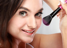 Beautiful woman smiling while applying blush on Royalty Free Stock Photo