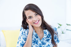 Beautiful woman smiling at camera sitting on her bed Stock Image