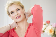 Beautiful Woman. Beautiful smiling elegant woman indoors wearing pink blouse and short blond hair Royalty Free Stock Image