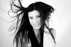 Beautiful woman smiling with hair blowing in the air Royalty Free Stock Photography