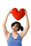 Beautiful woman smiling happy feeling in love holding red heart shape pillow Royalty Free Stock Image