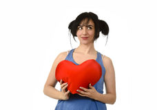 Beautiful woman smiling happy feeling in love holding red heart shape pillow Stock Image