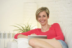 Beautiful woman smiling happy working at home with digital tablet computer pad Royalty Free Stock Photography