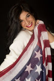 Beautiful woman smiling holding an American flag scarf Royalty Free Stock Image