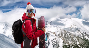Beautiful woman smiling and holding a snowboard Stock Photo