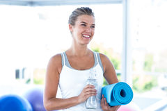 Beautiful woman smiling while holding water bottle and yoga mat Stock Images