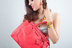 Beautiful woman smiling with jewelry and bag Royalty Free Stock Image