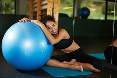 Beautiful woman smiling and leaning on an blue pilates ball at the gym Stock Photo