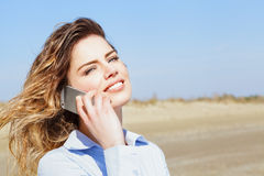 Beautiful woman smiling on the mobile phone Royalty Free Stock Image
