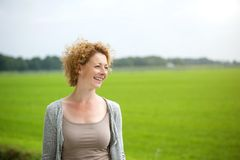 Beautiful woman smiling outdoors by green countryside Royalty Free Stock Photos