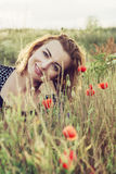 Beautiful woman is smiling and posing in poppy flowers field Stock Images