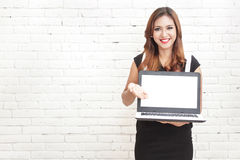 Beautiful woman smiling while presenting a brand new laptop Royalty Free Stock Photography