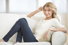 Beautiful Woman Smiling While Relaxing On Sofa Stock Images